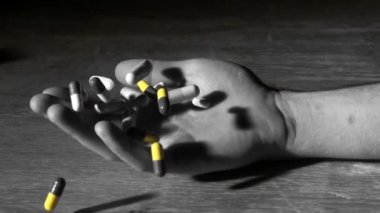 Mans hand falling holding pills after overdose in selective black and white — Stock Video