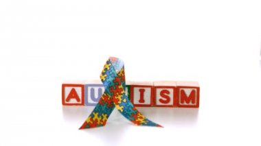 Awareness ribbon falling onto blocks spelling autism on white background — Stock Video