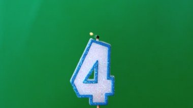 Four birthday candle flickering and extinguishing on green background — Stock Video