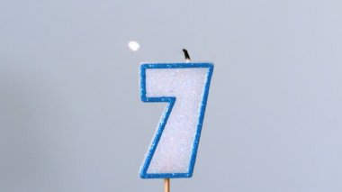 Seven birthday candle flickering and extinguishing on blue background — Stock Video
