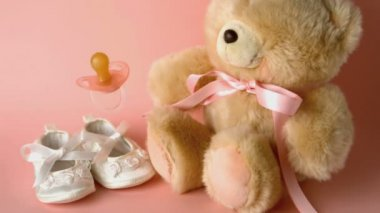 Pink soother falling in front of baby shoes and a teddy bear — Stock Video