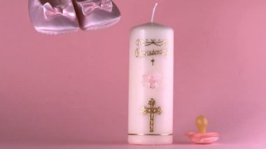 Baby shoes falling beside baptism candle and pacifier — Stock Video