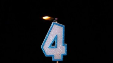 Four birthday candle flickering and extinguishing on black background — Stock Video