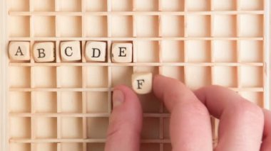 Hand spelling out the alphabet in wooden dice on a grid — Stock Video