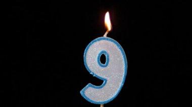 Nine birthday candle flickering and extinguishing on black background — Stock Video