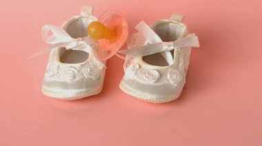 Pink soother falling onto baby shoes — Stock Video