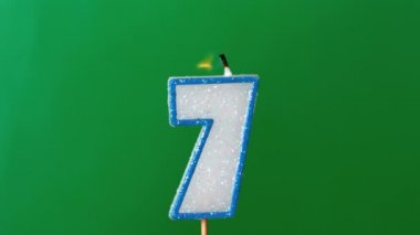 Seven birthday candle flickering and extinguishing on green background — Stock Video