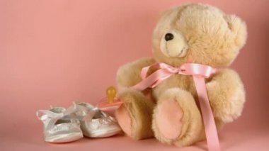 Pink soother falling onto a teddy bear and baby shoes — Stock Video