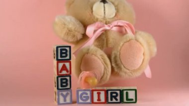 Teddy bear falling onto blocks spelling baby and girl, and onto pink soother in slow motion