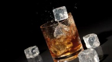 Three ice cubes falling into tumbler of whiskey and ice — Stock Video