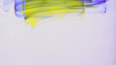 Yellow and purple ink swirling in water — Wideo stockowe