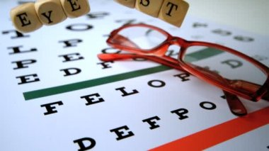 Eye test dice falling onto eye test with red reading glasses — Stock Video