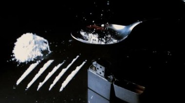 White drugs falling onto spoon beside lines larger pile and lighter — Stock Video