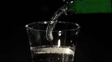 Bottle pouring fizzy water into glass — Stock Video