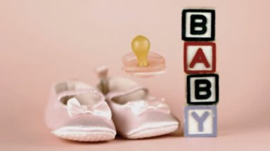 Pink soother falling in front of baby shoes and baby blocks — Stock Video
