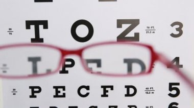 Red glasses held up to read eye test — Stock Video