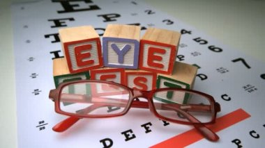 Glasses falling onto eye test with wooden blocks spelling out eye test — Stock Video