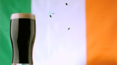 Shamrock confetti falling beside pint of stout — Stock Video