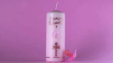 Pink pacifier falling beside baptism candle on pink background — Stock Video