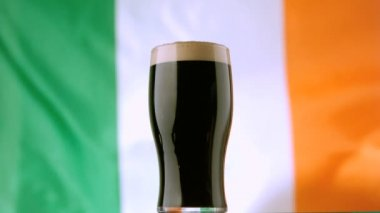 Pint of Irish stout on background of irish flag waving — Stock Video
