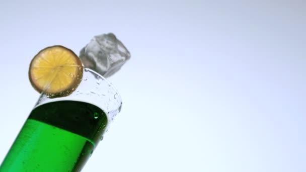Hielo que cae en copa de cóctel verde — Vídeo de stock