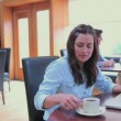 Brunette drinking coffee and using laptop — Stock Video