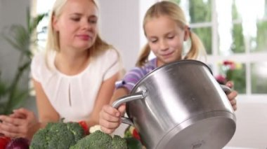 Mother and daughter putting vegetables in a pan — Stock Video