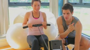 Happy woman at the rowing machine supporting by a coach — Stock Video