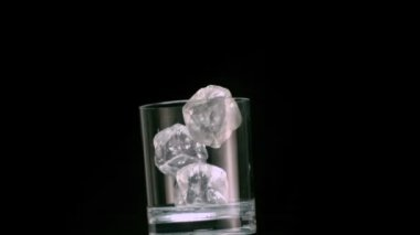Three ice cubes falling into a glass — Stock Video