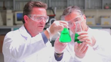 Two chemists experimenting with the green liquid in beakers — Stock Video