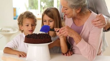 Grandmother icing cake with grandchildren — Stock Video