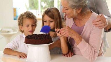 Grandmother icing cake with grandchildren — Stock Video