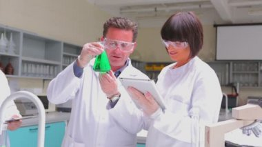 Chemist mixing green liquid in beaker with two chemists watching — Stock Video