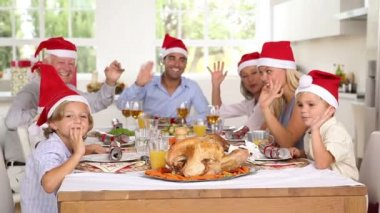 Family around the dinner table at christmas wearing santa hats and waving