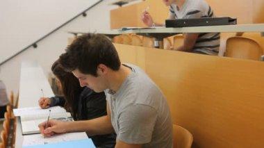 書いている間に座っている学生 — ストックビデオ