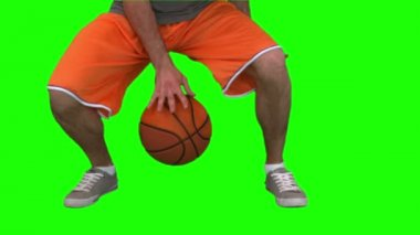 Man dribbling a basketball against green background — Stock Video