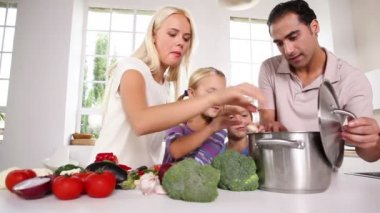 Posing family putting vegetables in a pot — Stock Video