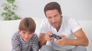 Father and son playing video games together — Stock Video