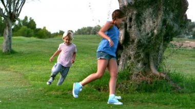 Little girl and little boy running around a tree — Stock Video