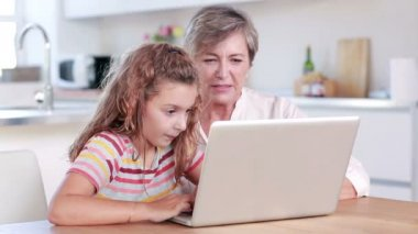 Child using laptop with her grandmother — Stock Video