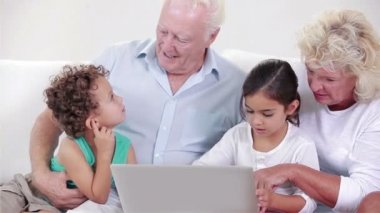 Two grandparents and two children using a laptop — Stock Video