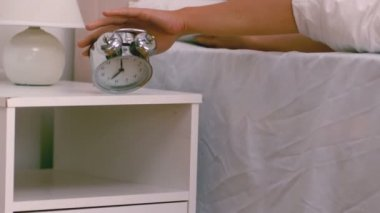 Lazy woman pushing down her alarm clock — Stock Video