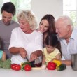 Granny cutting vegetables with the family around — Stock video