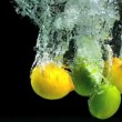 Stock Video: Lemons and limes dropping into water