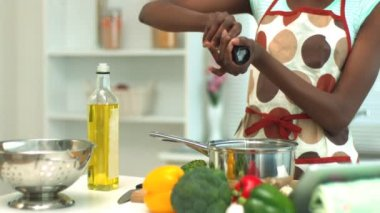 Woman adding pepper to saucepan — Stock Video