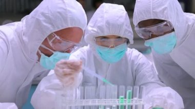In protective suits adding green liquid to test tubes with two other chemists watching — Vidéo