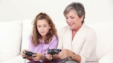 Grandmother playing at the video games with his granddaughter — Stock Video