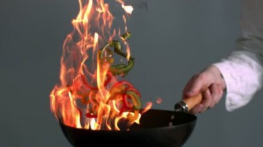 Peppers burning in a pan with big flame in slow-motion — Stock Video