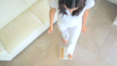 Woman standing on bathroom scales — Stock Video