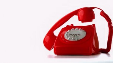 Receiver falling onto a red dial phone on white background — Vidéo